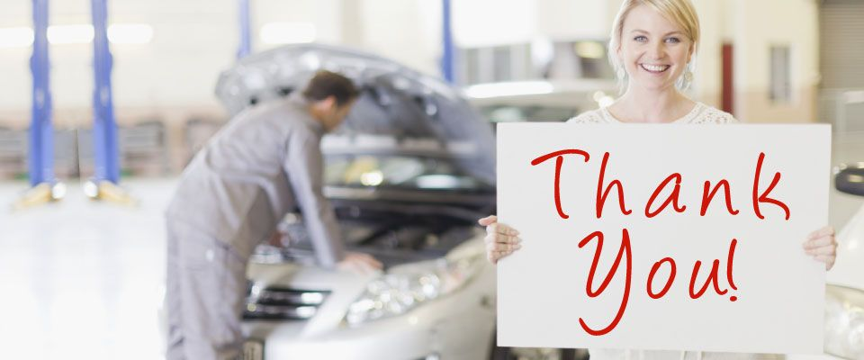 "Woman at auto shop holding a sign saying ""Thank You!"""